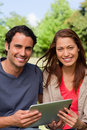 Man and a woman look ahead while holding a tablet Stock Photos