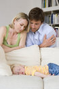 Man and woman looking at daughter months asleep on sofa close up women Royalty Free Stock Photography