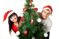 Man and woman looking out of Christmas tree Stock Images