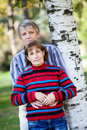 Man and a woman of middle age standing in park with his back to a tree women the Stock Image