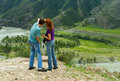 Man woman nature landscape young couple caucasian men and among the looking at the beautiful with mountains showing something to Royalty Free Stock Images