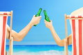 Man and woman relaxing on a beach and cheering with beer women bottles next to sea Royalty Free Stock Images