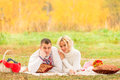 Man and woman relaxing comfortably on the plaid women in park Royalty Free Stock Photos
