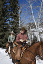 Man and Woman Riding Horses in the Snow Stock Photos