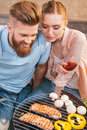 Man and woman roasting meat and vegetables on barbecue grill Royalty Free Stock Photo