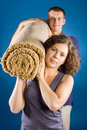 Man and woman with rolled carpet Stock Image