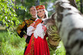 A man and a woman in the Russian festive national dress on the background of the forest Royalty Free Stock Photo