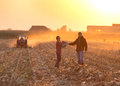 Man and woman shaking hands young women men in the field in sunset while tractor baling straw Royalty Free Stock Images