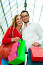 Man and woman in shopping mall with bags Stock Photos