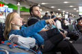 Man and woman sitting at airport terminal and pointing Royalty Free Stock Photo