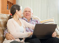 Man and woman sitting on couch with laptop happy mature couple using at home Royalty Free Stock Photos