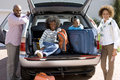 Man and woman by son and daughter in back of car with luggage smiling portrait women Royalty Free Stock Images