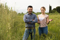 Man and woman standing in green wheat field Royalty Free Stock Photo