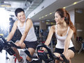 Man and woman talking in gym young men women while exercising on bicycle fitness center Stock Photos