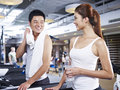 Man and woman on treadmill young men women talking during a break in gym Royalty Free Stock Photography