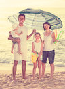 Man and woman with two kids standing together under beach umbrel