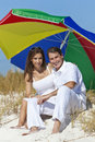 Man & Woman Under Colorful Umbrella on Beach Royalty Free Stock Photo