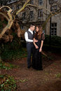 Man and woman in victorian clothing embracing in the park boy girl holding each other front of a house trunks of trees Royalty Free Stock Photo