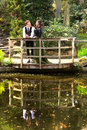 Man and woman in victorian fashion near lake with reflections in park women or edwardian vintage clothing the the water on a Royalty Free Stock Photos
