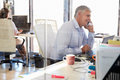 Man at work talking on phone, office interior Royalty Free Stock Photo