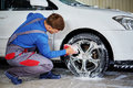 Man worker washing car`s alloy rims on a car wash Royalty Free Stock Photo