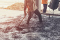 Man workers spreading freshly poured concrete mix on building Royalty Free Stock Photo