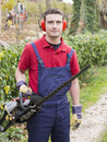 Man working bush trimmer portrait wearing ear protectors trimming the in the backyard with petrol Stock Photos