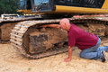 Man working on excavator track Stock Photography