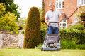 Man Working In Garden Cutting Grass With Lawn Mower Royalty Free Stock Photo