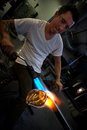 Man working at a glass company with blowtorch Stock Images