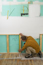 Man working on kitchen remodel measuring with tape measure while a Royalty Free Stock Image