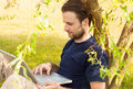 Man working on laptop computer outdoor in a park happy smiling forty years old caucasian while sitting by tree during sunny Stock Photos
