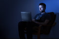 Man working on a laptop in a dark room at night Royalty Free Stock Photo