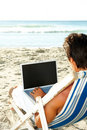 Man working on a laptop while relaxing on a beach Stock Photography