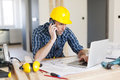 Man working on laptop talking mobile phone and using construction side Stock Photography