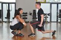 Man working out with his pesonal trainer while female personal instructor assisting him Royalty Free Stock Images