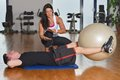 Man working out with his pesonal trainer while female personal instructor assisting him Royalty Free Stock Photography