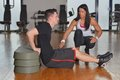 Man working out with his pesonal trainer while female personal instructor assisting him Royalty Free Stock Image