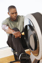 Man working out on rowing machine young african american in health club Royalty Free Stock Photos