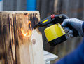 Man working outdoor. Man roasting wooden boards with gas-burner Royalty Free Stock Photo
