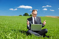 Man working outdoors in nature on his laptop giving a thumbs up gesture of approval with both hands Stock Image