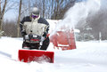A man works snow blowing machine