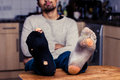 Man with worn out socks relaxing in kitchen young is resting his feet on his dinner table the he is wearing Stock Image