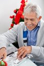 Man wrapping christmas gift happy senior at home Royalty Free Stock Images