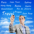 Man writing the names of travel destinations young on an imaginary board international with sky as background Stock Photography