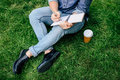 Man writing on notebook and drinking coffee from paper cup while sitting on green grass Royalty Free Stock Photo
