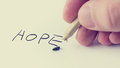 Man writing the word Hope on notepaper