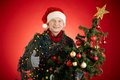 Man with xmas tree portrait of happy in santa cap decorated showing thumb up Royalty Free Stock Images