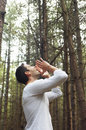 Man yelling all alone in woods low angle side view of a young standing and Royalty Free Stock Photography