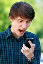 Man is yelling on his cell phone young attractive outdoors in the park Royalty Free Stock Photography